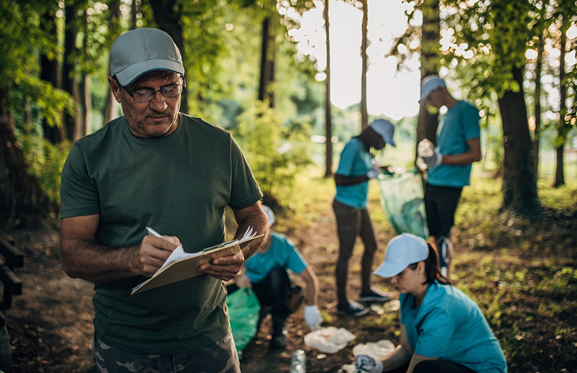 man in woods with volunteers