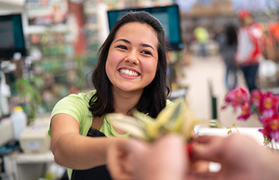 smiling woman giving a customer a product
