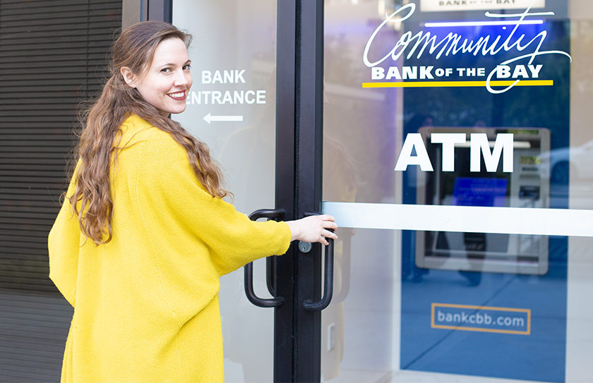 woman opening door to an enclosed ATM
