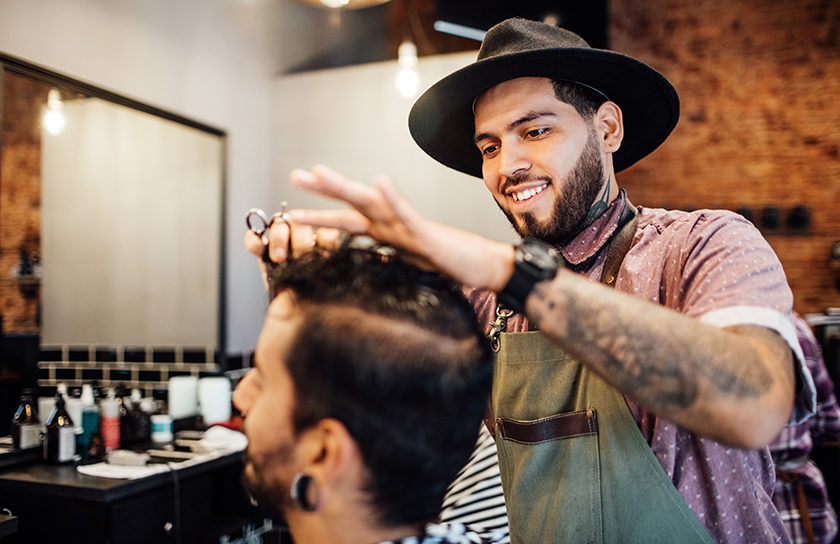 smiling man in hat cutting another mans hair