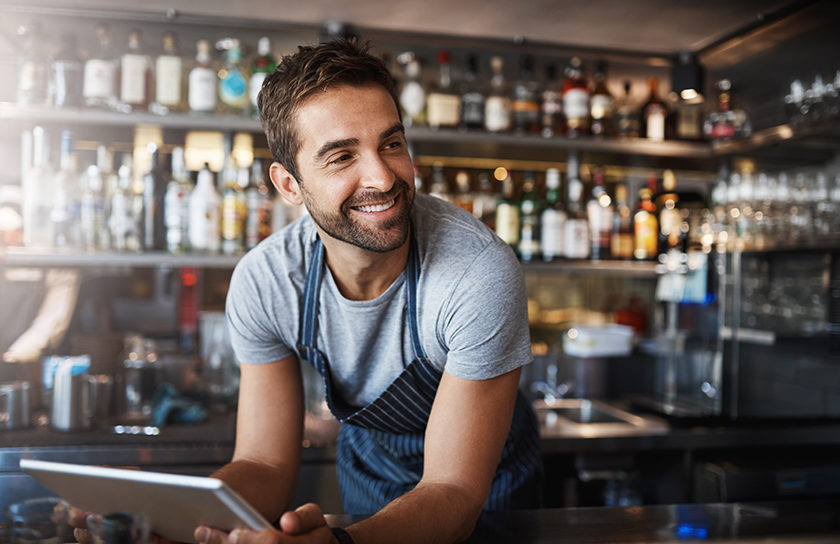 smiling bearded man working in cafe