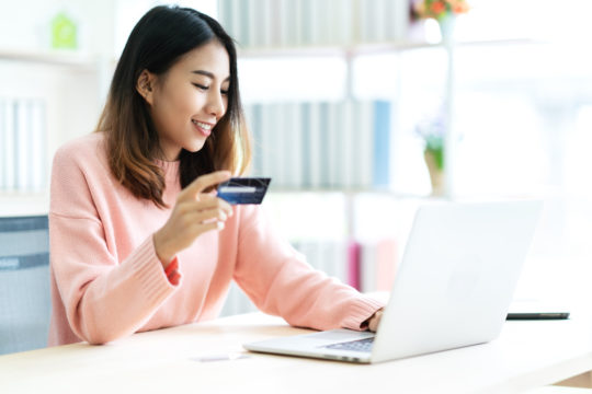 woman holding credit card sitting at table