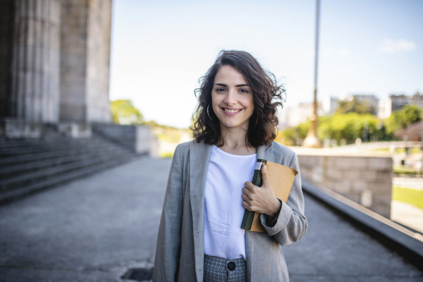 woman standing smiling with books