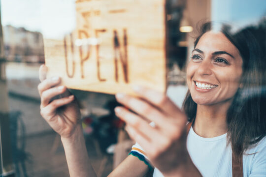 Portrait of a happy business owner hanging an open sign