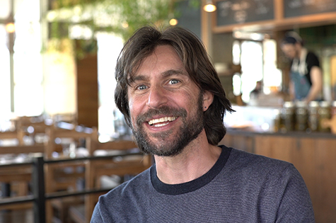 bearded smiling man sitting in cafe