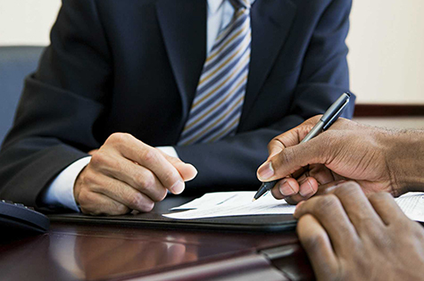 close up of two people signing a form