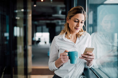 woman holding blue coffee mug while viewing phone screen